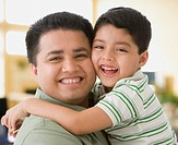 Close up of Hispanic father and son hugging
