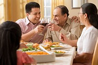 Hispanic father and adult son toasting at dinner table