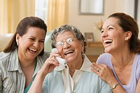 Hispanic grandmother, mother and daughter with telephone (thumbnail)