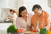 Hispanic woman and adult daughter chopping vegetables