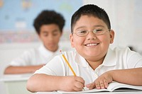 Hispanic boy writing at school desk