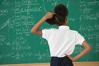 African American girl looking at blackboard (thumbnail)