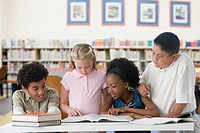 Multi-ethnic children studying in school library