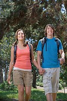 Couple with backpacks holding hands
