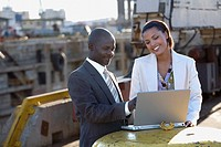 African American businesspeople looking at laptop