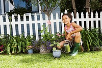 Gardening girl watering plant next to picket fence