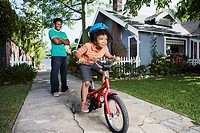 Father teaching boy to ride bicycle