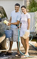 Multi-ethnic couple washing car