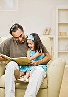Mixed Race father reading to daughter