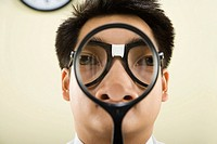 Nerdy Asian man holding magnifying glass in front of face