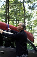 Man securing canoe to roof rack