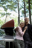 Couple standing in front of SUV in the woods