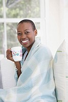 Woman wrapped in a blanket drinking coffee