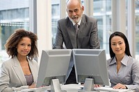 Multi-ethnic businesspeople behind computers