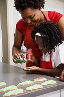 African mother and daughter decorating cookies