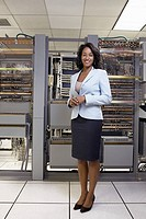 Businesswoman standing by computer servers (thumbnail)