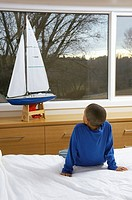 Young boy watching miniature sailboat