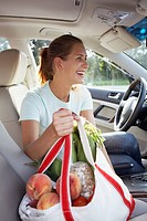 Woman in car with groceries
