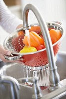 Woman washing peppers in strainer (thumbnail)