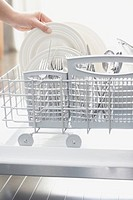 Woman removing plate from dishwasher rack