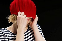 Woman covering face with red beret