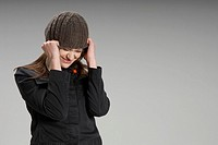 Woman pulling hat over head (thumbnail)
