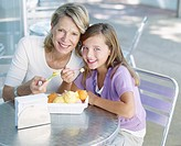 Woman and young girl on outdoor patio eating ice cream