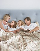 Family in bed together bonding