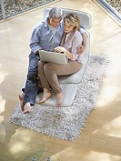 Couple in chair together with laptop indoors