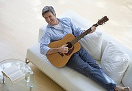 Man in living room playing acoustic guitar