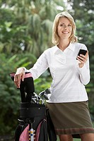 Woman outdoors with golf clubs and her mobile phone