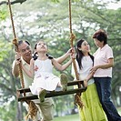 Family outdoors at park with young girl on swing (thumbnail)