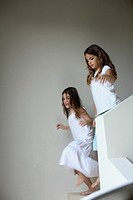 Two young girls in corridor by staircase