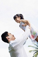 Man lifting up young girl outdoors