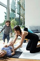 Woman in living room playing with three young kids