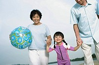 Couple and young girl outdoors on beach holding hands