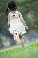 Young girl running towards swing outdoors at park