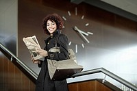 Businesswoman indoors on staircase with newspaper (thumbnail)