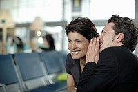 Man in airport whispering in woman's ear (thumbnail)