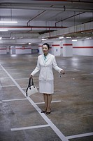 Businesswoman in indoor parking garage looking for her car