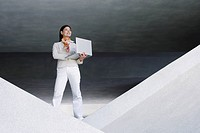 Businesswoman indoors standing in structure with laptop