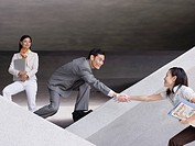 Businessman helping businesswoman over structure with businesswoman watching