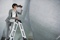 Businesswoman on ladder in structure using binoculars