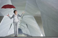 Businesswoman in structure holding umbrella