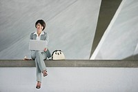Businesswoman sitting in structure with laptop