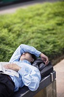 Businessman outdoors sleeping on a bench