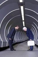 Two businessman in corridor bowing