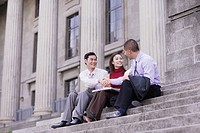 Three businesspeople outdoors on staircase