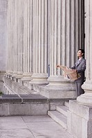 Businessman outdoors on steps with newspaper