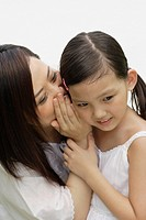 Woman indoors whispering in young girl's ear